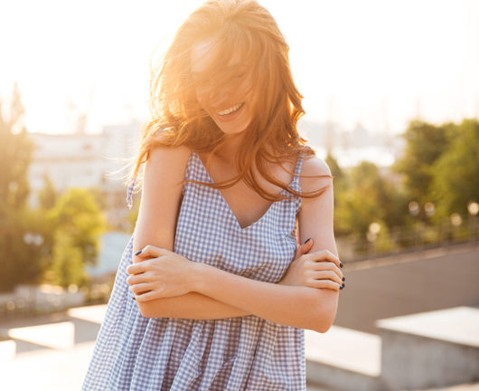 Smiling pretty girl standing with arms folded and laughing outdoors with a city view